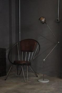 """Studio 900 Design, collezione Palation, """"Poltrona Novecento"""", poltrona in ferro, seduta e schienale in eco-pelle; """"Fener"""", antica lampada in ferro con base in marmo e faro di auto vintage anni '50 (courtesy Studio 900 Design)"""