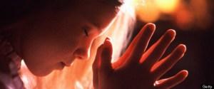 Girl (6-8) praying, profile, close-up