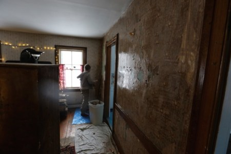 Jon's photo of me scraping wallpaper in the dining room.