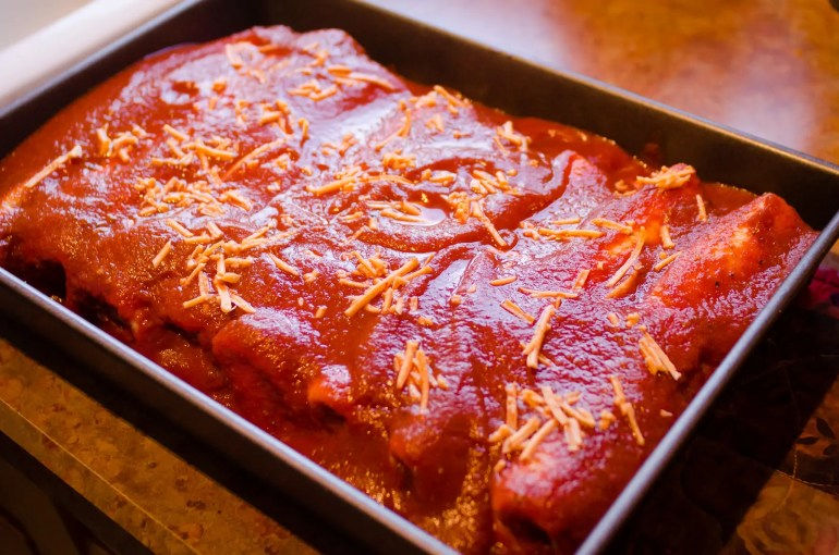 veggie enchiladas assembled, topped with sauce and shreds, and ready for the oven.
