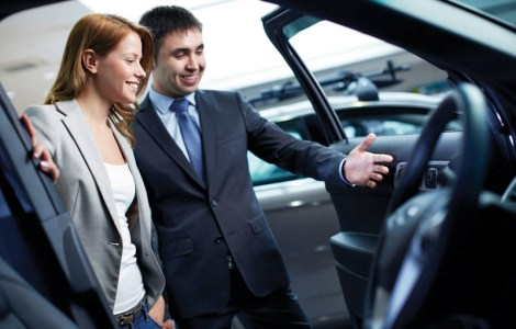 Photo of elegant woman listening to consultant in automobile center