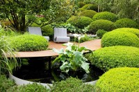 Patio under tree surrounded by mounds of clipped Buxus ...