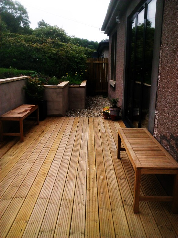 Timber Decking to patio doors with rendered walls and timber copings.