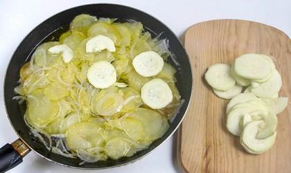 Añadiendo calabacín a las patatas y cebolla