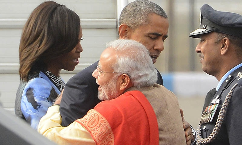 Indian Prime Minister Narendra Modi and U.S. President Barack Obama embrace, as first lady Michelle Obama speaks with an officer upon arrival at the Palam Air Force Station in New Delhi, India, Sunday, Jan. 25, 2015. Obama's arrival Sunday morning in the bustling capital of New Delhi marked the first time an American leader has visited India twice during his presidency. Obama is also the first to be invited to attend India's Republic Day festivities, which commence Monday and mark the anniversary of the enactment of the country's democratic constitution. (AP Photo)