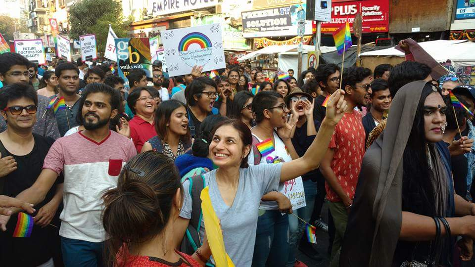 A participant waves at onlookers from buildings during Mumbai Pride 2017