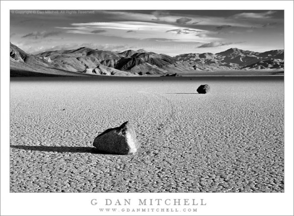 "Two Rocks, Morning, Racetrack Playa - Black and white photograph of two ""moving rocks"" on the Racetrack Playa at Death Valley National Park. Morning light with unusual clouds, and the Grandstand in the distance."