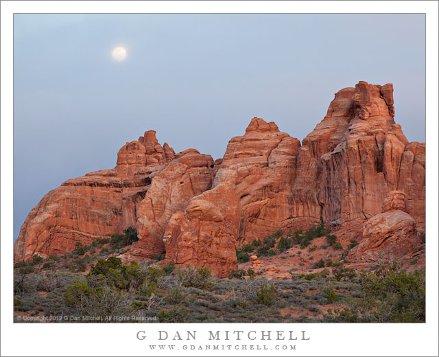 Sandstone Towers, Moon Rising Through Clouds - The full moon rises in a cloudy sky above sandstone towers, Arches National Park, Utah.