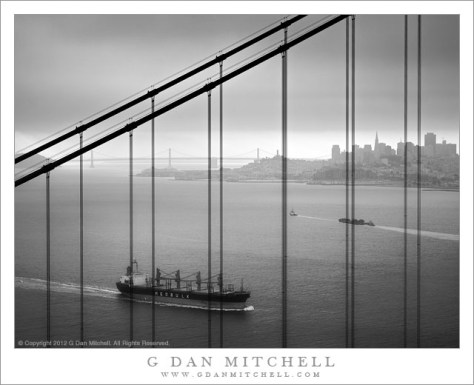 Ships, San Francisco Bay, Morning - Freighter departing San Francisco Bay on a foggy morning is seen through the cables of the Golden Gate Bridge with the San Francisco skyline in the background. Black and white photograph.