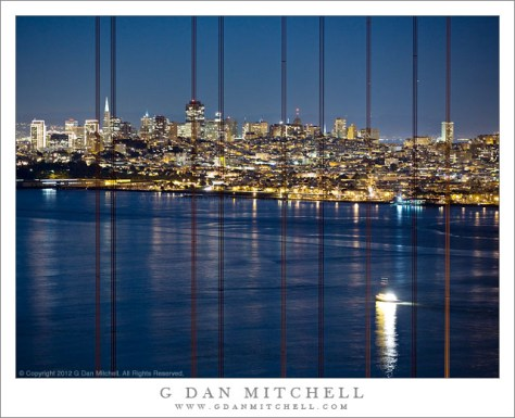 San Francisco Skyline, Golden Gate Bridge Cables, Night - Photograph of the night skyline of San Francisco shot through the cables of the Golden Gate Bridge. Holiday lighting on downtown buildings.