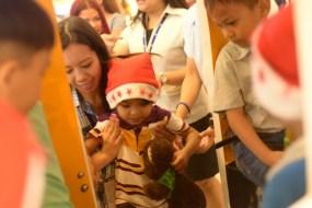 An SM employee lifts a kid onto a mall ride.