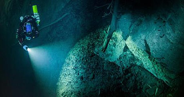 In this underwater photo taken Aug. 15, 2015 in the flooded Hranicka Propast, or Hranice Abyss, in the Czech Republic is seen Polish explorer Krzysztof Starnawski exploring the limestone abyss and preparing for deeper exploration with the use of a remotely-operated underwater robot, or ROV. On Sept. 27, 2016, the robot went to the record depth of 404 meters (1,325 feet) revealing the abyss to be the world's deepest flooded cave, during the 'Hranicka Propast - step beyond 400m' expedition led by Starnawski and partly funded by the National Geographic. Credit: Krzysztof Starnawski of EXPEDITION via AP
