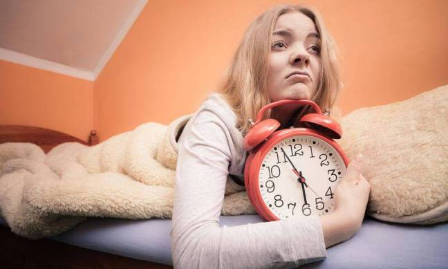 bigstock-Unhappy-Girl-In-Bed-With-Alarm-77119898