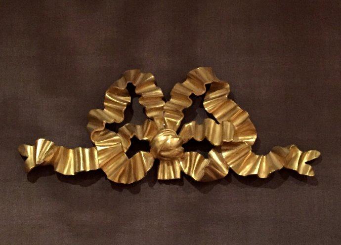 Ruban. En tilleul, sculpté et doré à la feuille d'or, dorure à l'eau avec brunissage à la pierre d'Agathe. Perruque autorisée, atelier de restauration du Château de Versailles, circa 1978. H. 28 x 44 cm.
