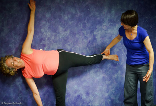 A woman with curly gray hair and glasses poses in  half moon yoga posture against a blue wall, while the teacher guides her leg position