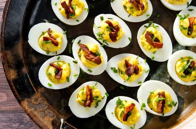 Deviled eggs are always a favorite appetizer. These creamy deviled eggs are topped with crispy bacon and fresh chives - they are sure to disappear fast! | girlgonegourmet.com