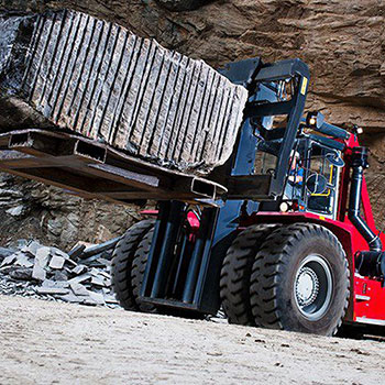 Picture showing a Kalmar Heavy Truck lifting a heavy load.