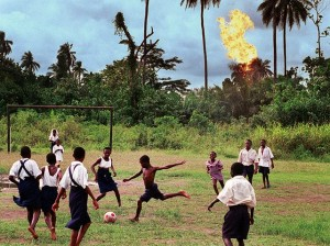 Schoolchildren in the Nigerian village of Akaraolu play football while the nearby Oshie gas flare roars. Photograph: Chris Hondros