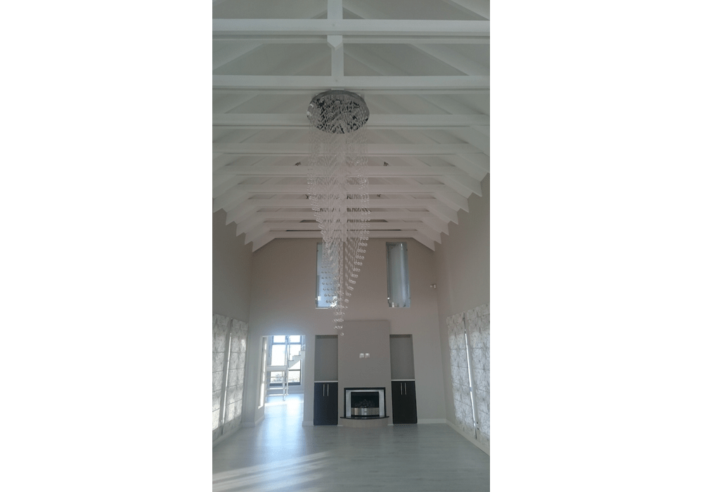 Exposed roof trusses with chandelier