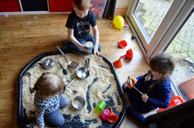 kids playing in tuff spot with oats
