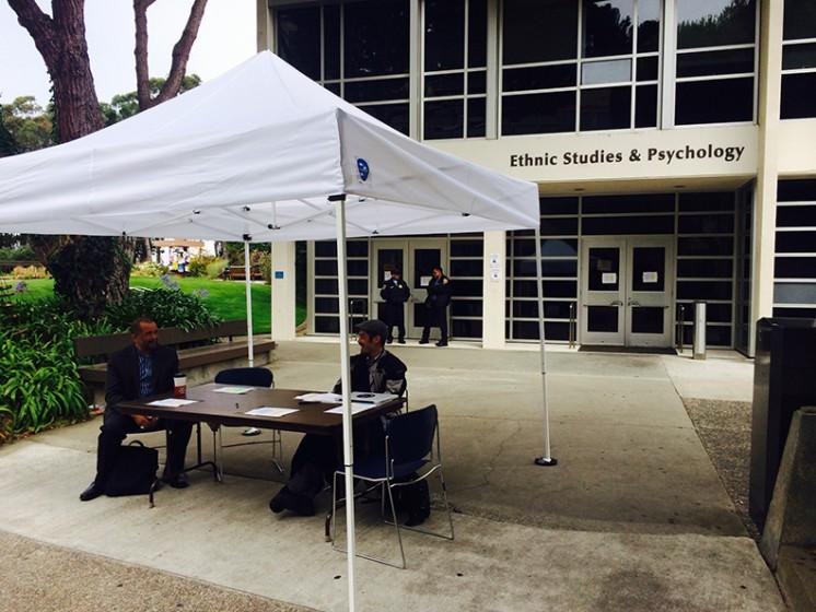 Campus representatives sit at an information booth providing class relocation information outside the Ethnic Studies and Psychology Building Thursday, Aug. 28.