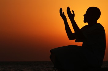 A man raises his hands to pray near the sea at sunset after a day of fasting in the holy month of Ramadan in Benghazi, Libya, on July 24, 2012