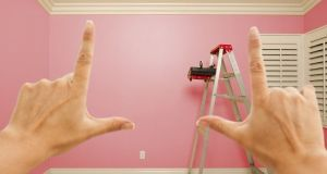 Hands Framing Pink Painted Room Wall Interior with Ladder, Paint Bucket and Rollers.