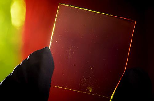 Modul panel surya transparan dengan berbagai warna konsentrator panel surya konvensional di latar belakang. Foto: G.L. Kohuth/msutoday.msu.edu