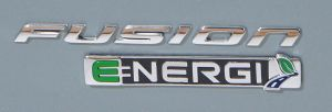 Ford Fusion Energi badge WAS 2012 0572 300x102 Ford Fusion Energi – The 620 Mile Bid to Win the Hybrid War