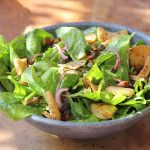 baby spinach salad with pita croutons, almonds and dates