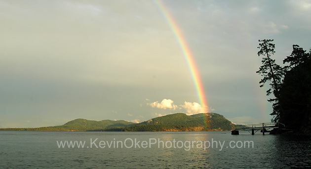A rainbow touches down over Saturna Island, Plumper Sound, North Pender Island, British ColumbiaRainbow over Saturna Island, North Pender Island, BC