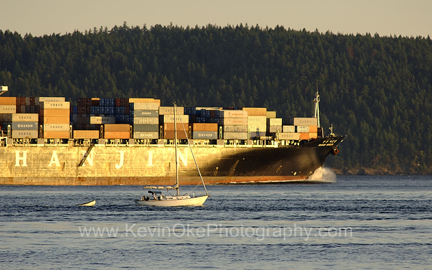 Headed for Asia, a freighter passes a sailboat on the way to the Juan de Fuca Strait. South Pender Island, BC