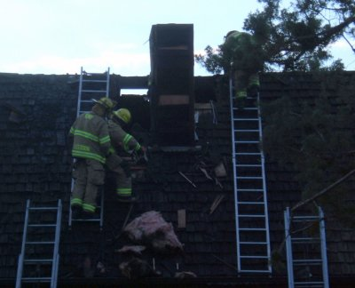 Fire fighters clearing the roof after a house fire