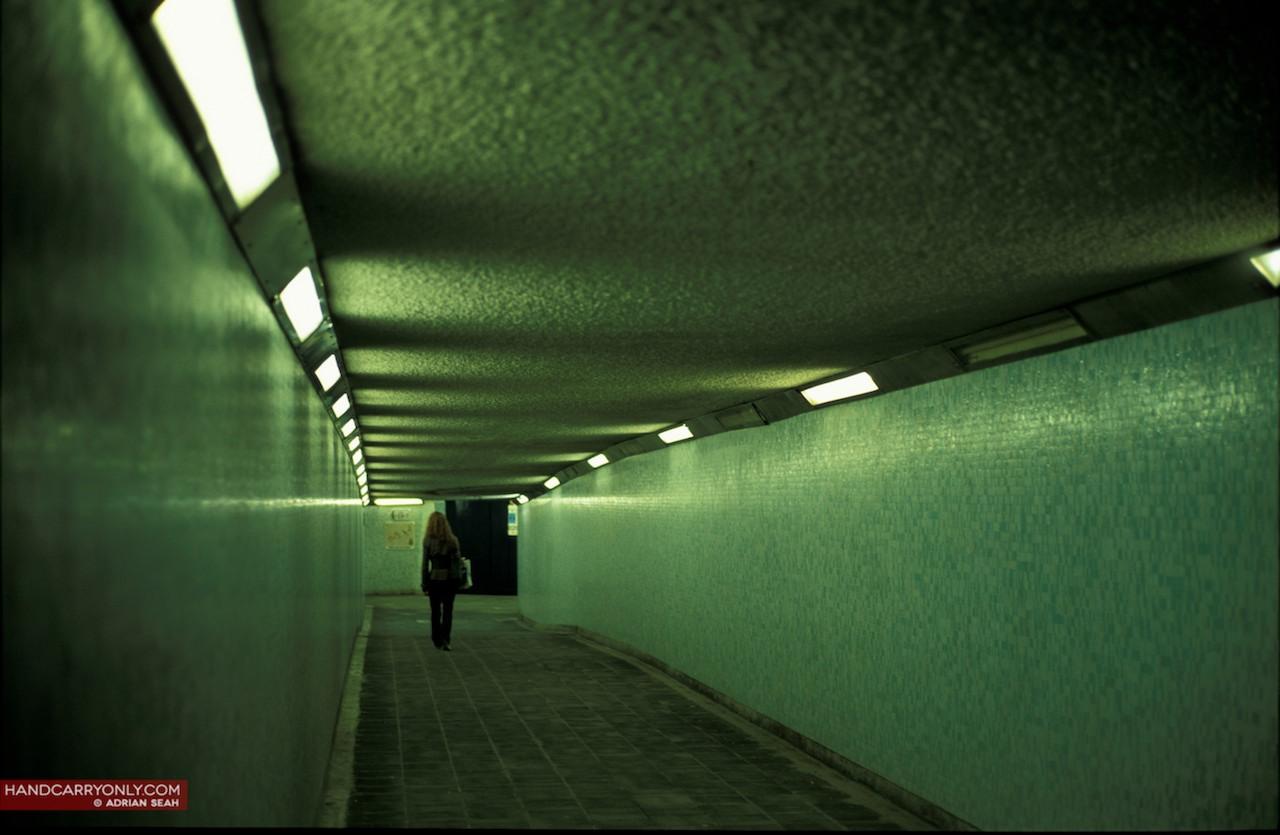 girl walking down dimly lit tunnel