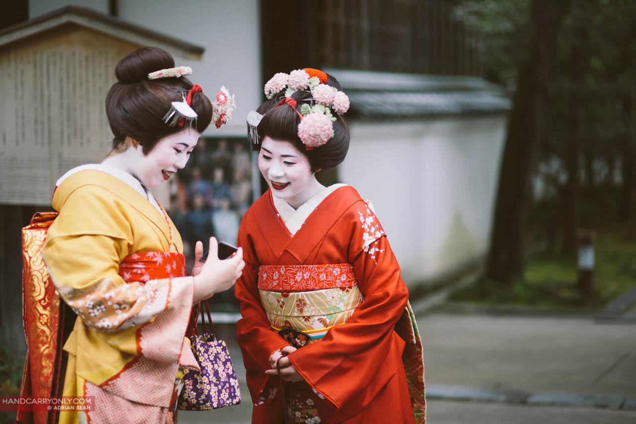 maiko looking at photo kyoto japan