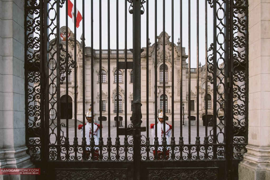 Soldiers in ceremonial dress stand at attention behind the gates of the Government Palace