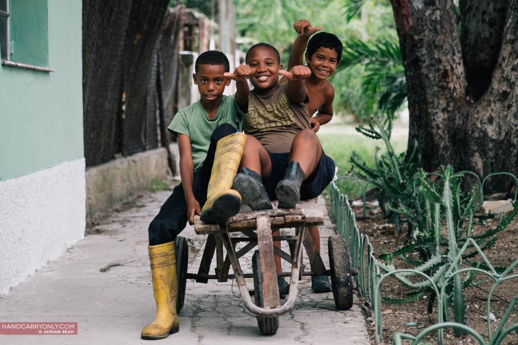 Three boys in the neighbourhood with their makeshift tricycle