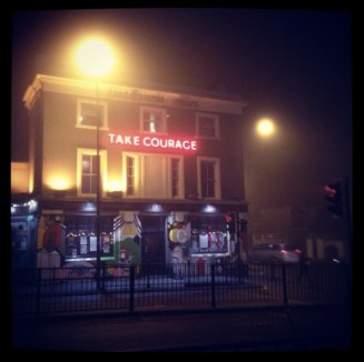 A picture of a pub in New Cross with a red neon sign that reads 'take courage'