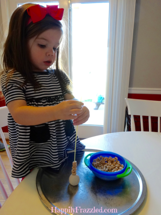 Stack Cheerios on uncooked spaghetti for an Indoor and Rainy Day Toddler Activity | HappilyFrazzled.com