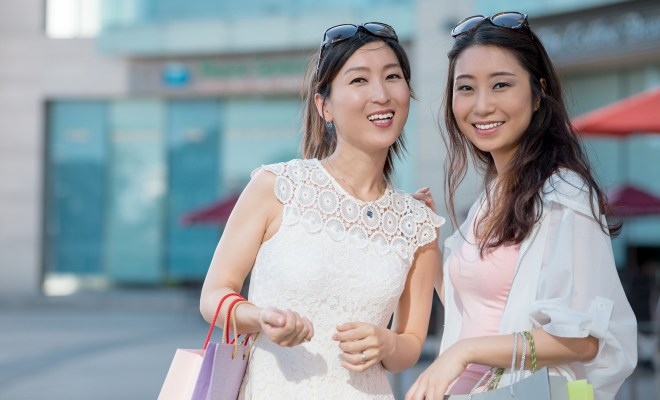 Portrait of two Korean female friends with shopping bags