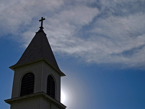 church steeple with cross on top against sky