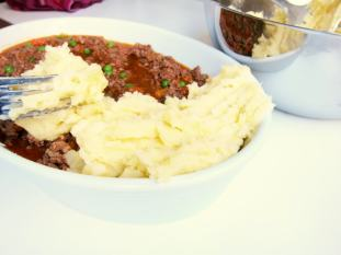 Using a fork, plop mounds of mashed potatoes starting at the edges and then and into a single layer.
