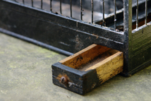 close up showing seed drawer detail on a black painted vintage canary cage