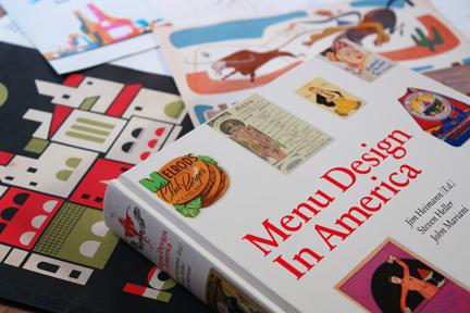 """""""Menu Design in America"""" book surrounded by vintage menus"""