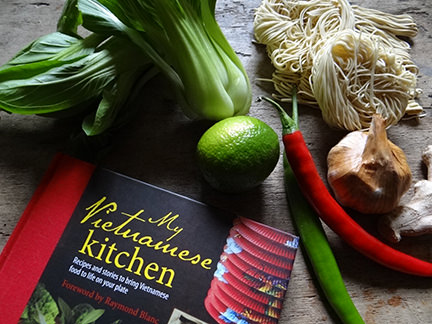 "cover of ""My Vietnamese Kitchen"" cookery book with dried noodles, pak choi, lime, chilli, ginger and garlic"