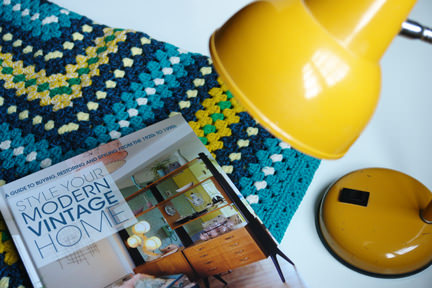 Style Your Modern Vintage Home book with vintage crocheted blanket and bright yellow goose neck desk lamp