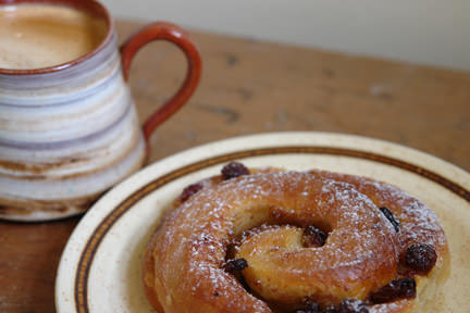 pain aux raisins on a plate with cup of coffee