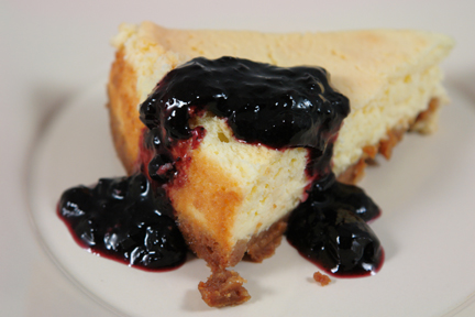 slice of baked vanilla cheesecake made from a Gordon Ramsay recipe served with a wild blueberry preserve