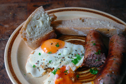sliced, homemade ciabatta with fried eggs and Todmorden-made sausages