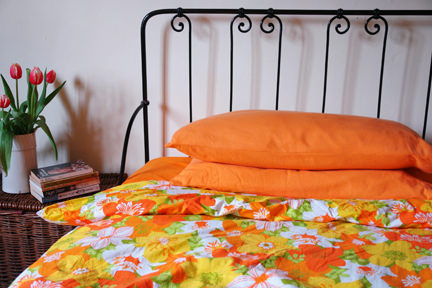 view of our craft & sewing room showing a vintage black painted iron bed with vintage floral quilt cover in shades of orange & yellow